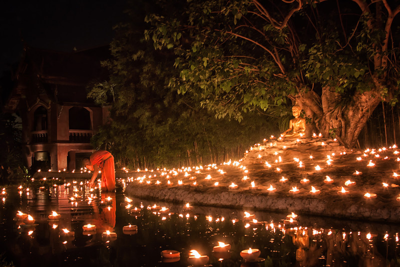 A monk lighting up candles in a pond during Visakha Bucha night in Chiang Mai, Thailand.