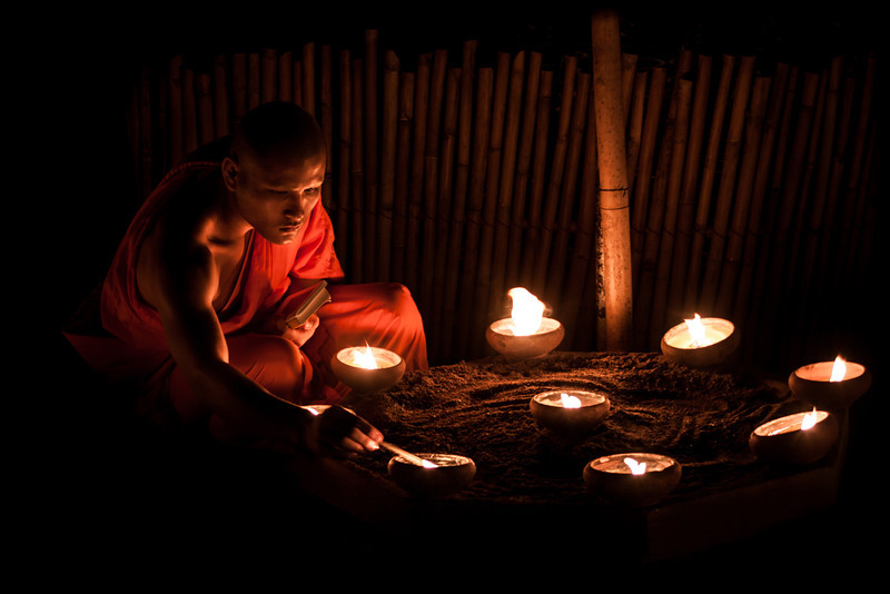 A monk slowly lighting up candles during Asalaha Bucha in Chiang Mai, Thailand.