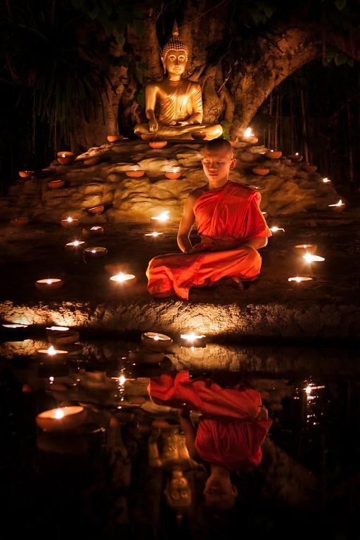 A young monk meditating during Visakha Bucha in Chiang Mai, Thailand.