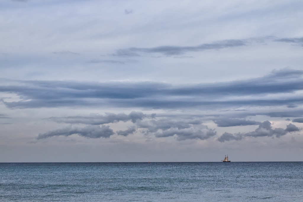 A sailboat on the horizon in Barcelona, Spain.