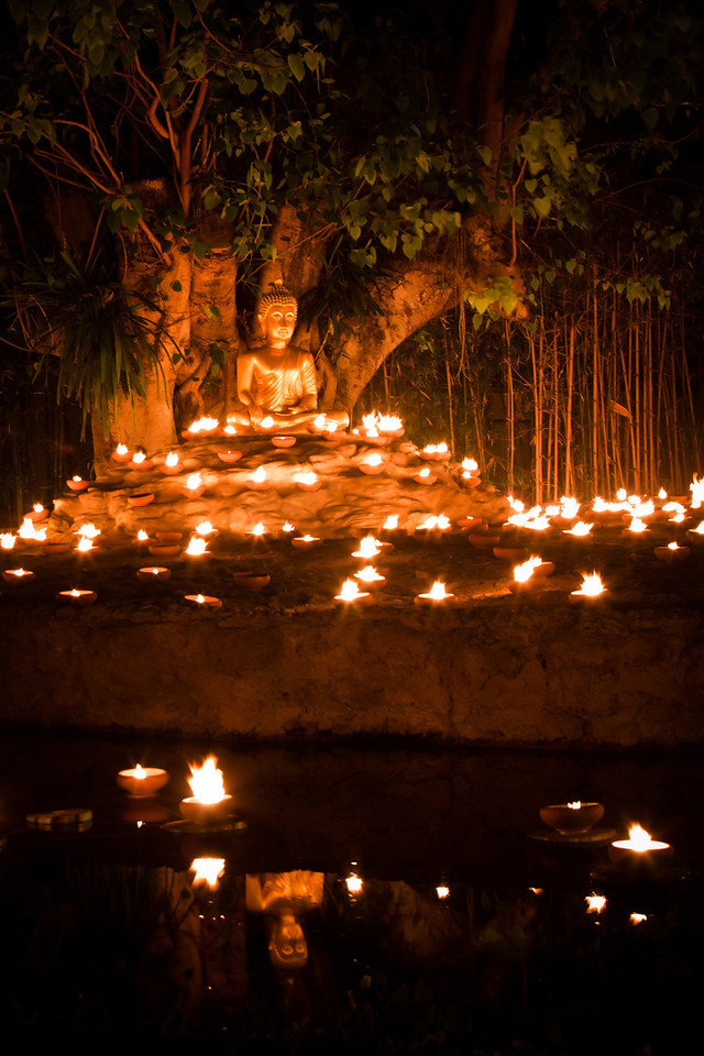 Golden Buddha statue decorated with candles in Chiang Mai.