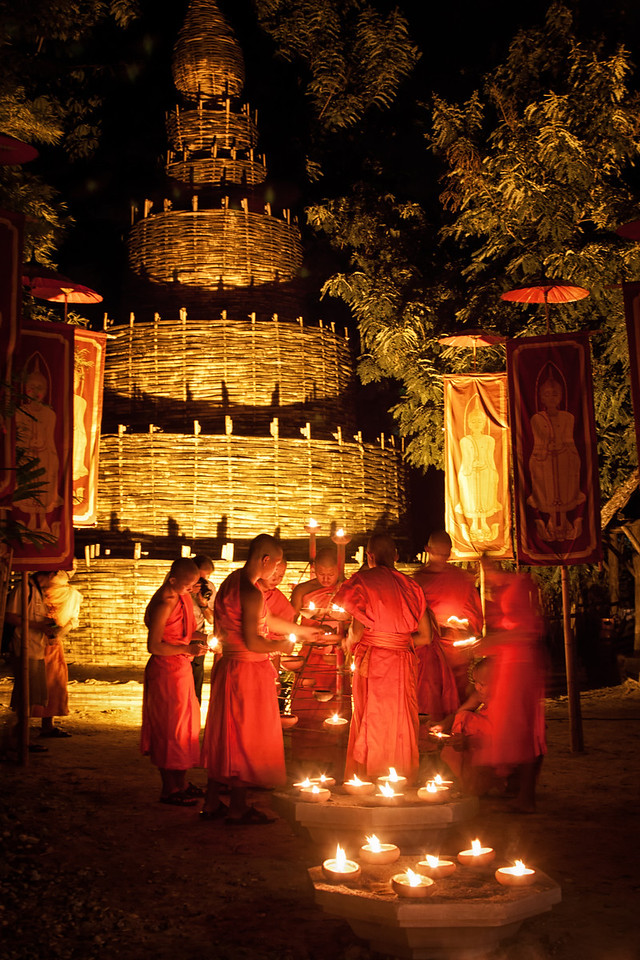 Young monks lighting candles next to a bamboo chedi in Chiang Mai, Thailand.