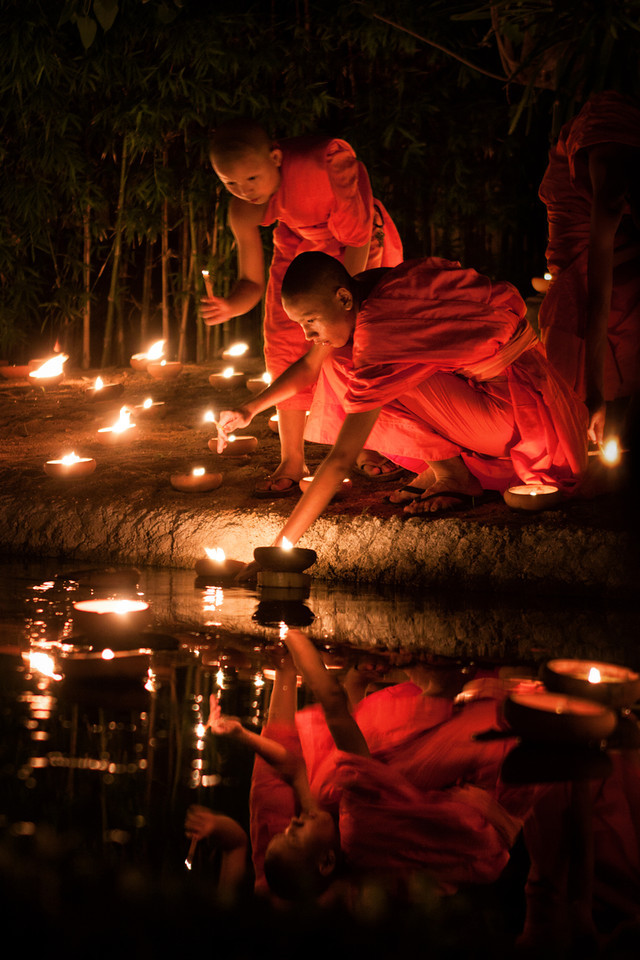 Young Monks lighting candles in a pond during Visakha Bucha in Chiang Mai, Thailand.