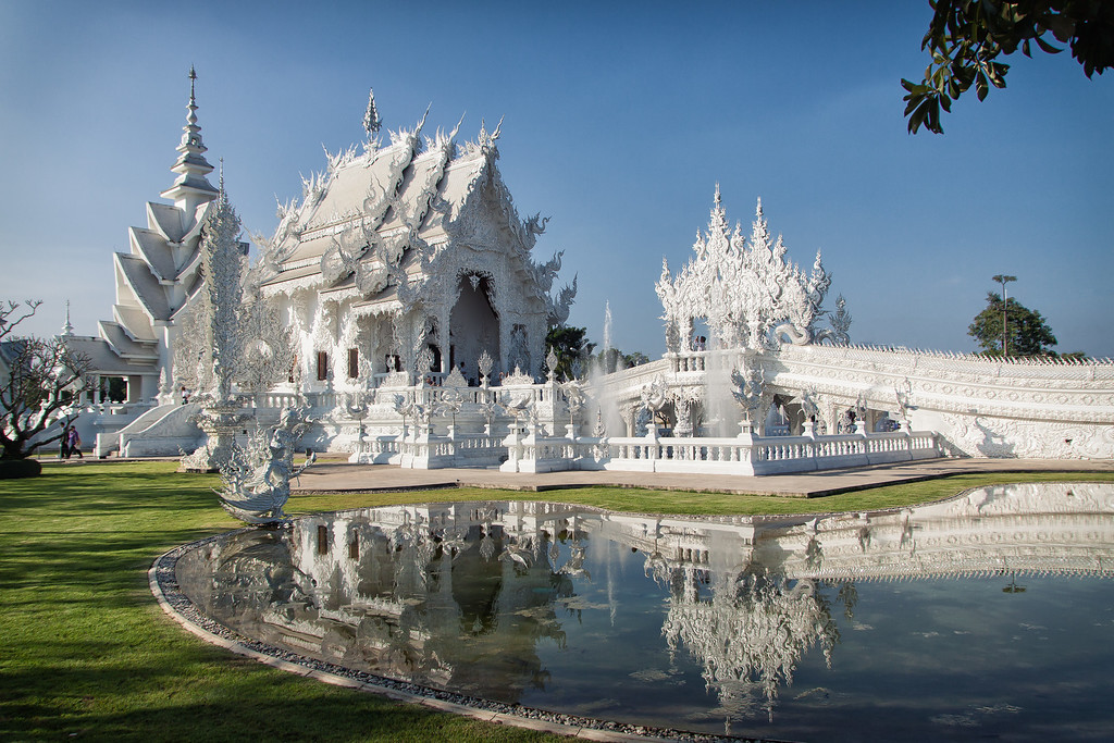 The White Temple glitters under the sun in Chiang Rai, Thailand.