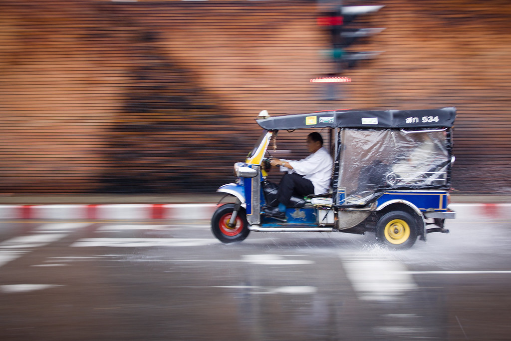 A panning shot of a speeding tuk tuk in the rain in Chiang mai, Thailand.