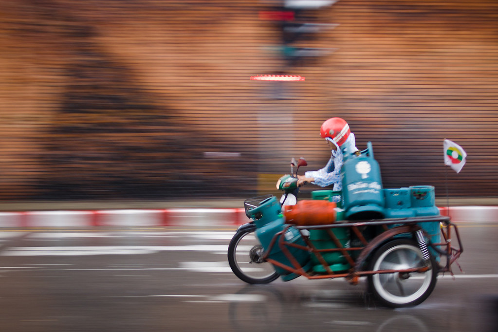 A speeding scooter under the rain carrying gas tanks in Chiang Mai, Thailand.