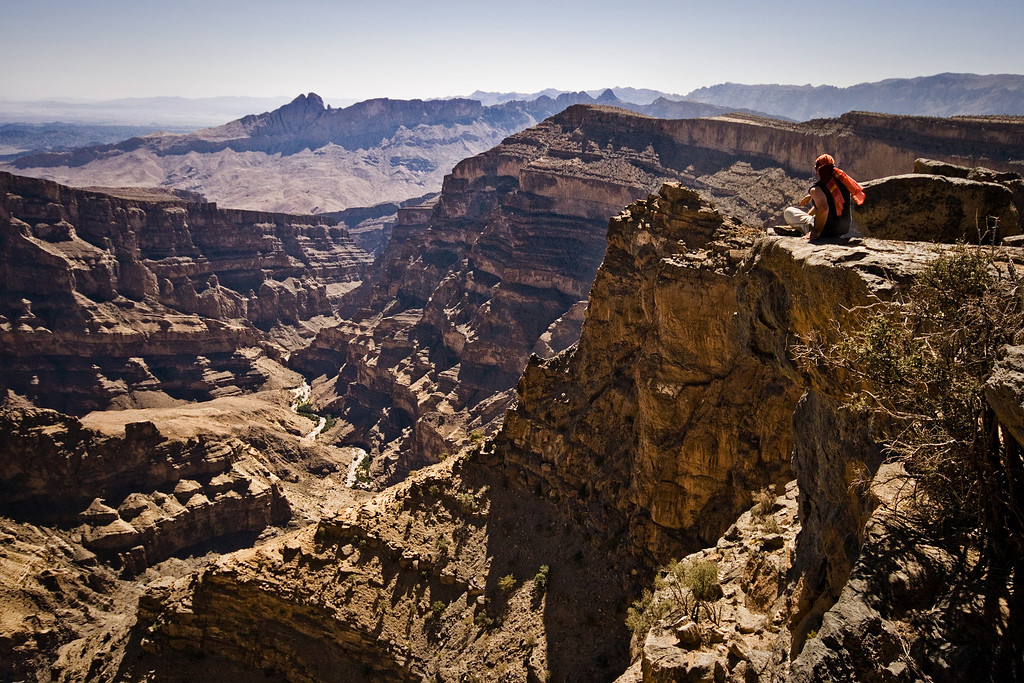 A young man sitting at the edge of the Wadi Nakhr Canyon in Jabal Shams, Oman.
