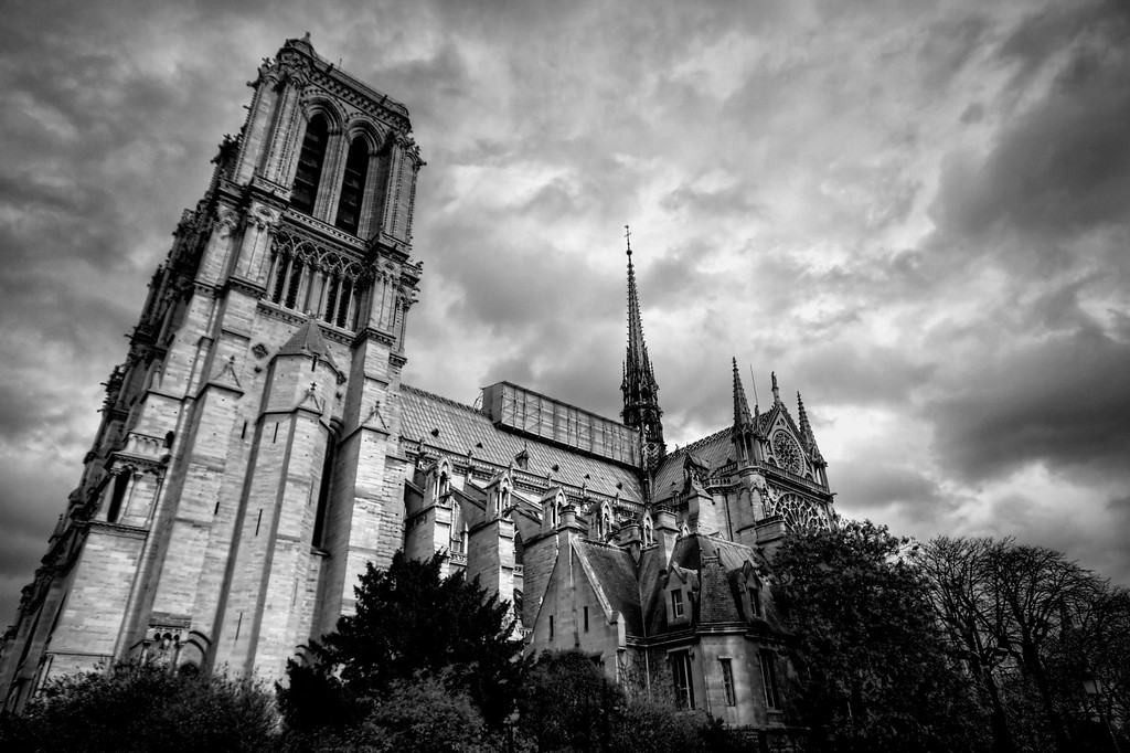 A black and white side shot of the Notre-Dame cathedral, one of the most famous icons of the city of Paris in France.