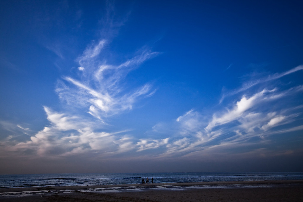 A family hanging out at one of the beaches North of Amsterdam in the Netherlands with a beautiful evening sky.
