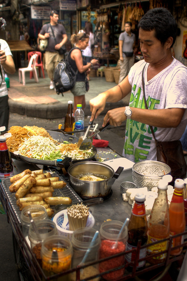 A Thai man cooking pad thai noodles in the streets of khao san road in Bangkok, Thailand