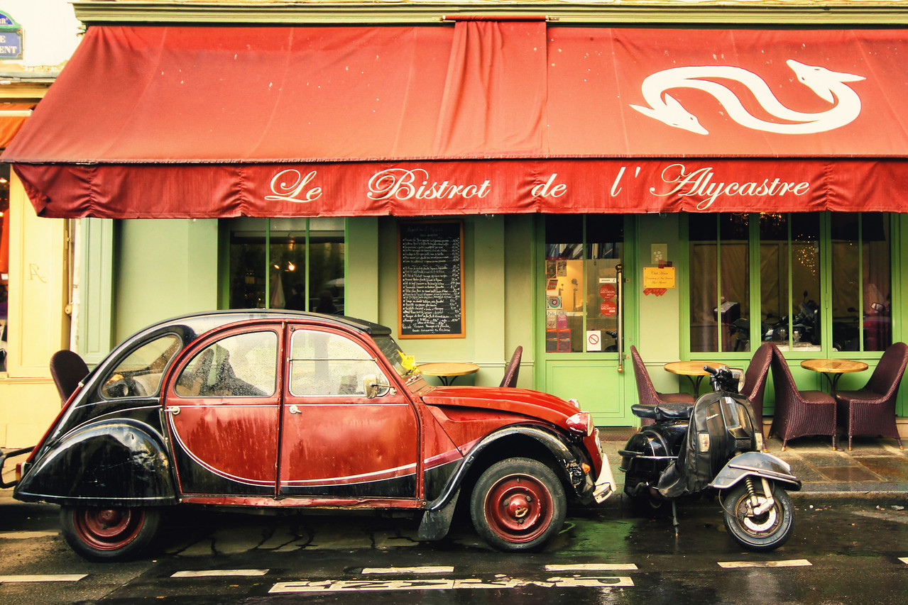 An old red deux cheveaux Citroen car in front of a Parisian bistrot cafe in the streets of Paris, France