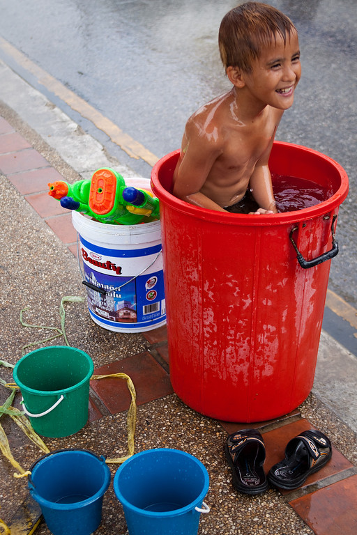 A little kid sitting in a bucket full of water during Songkran in Chiang Mai, Thailand.