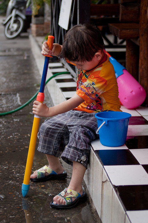 A little kid trying to pump water from the puddle on the floor during Songkran in Chiang Mai.