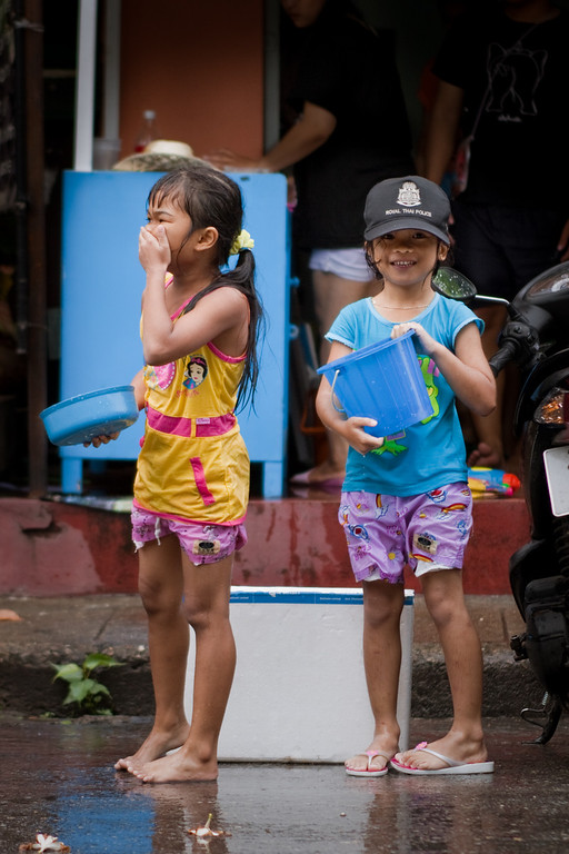 Two cute girls playing with water during Songkran in Chiang Mai, Thailand