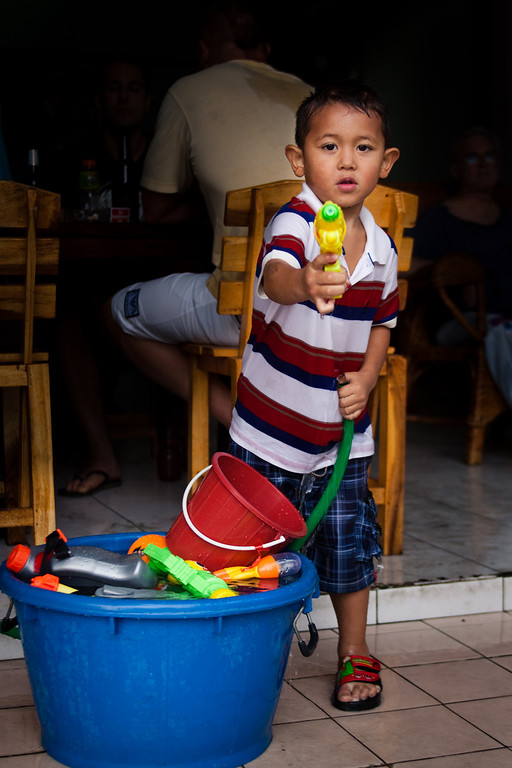 A kid spraying water with his gun during Songkran in Chiang Mai, Thailand.