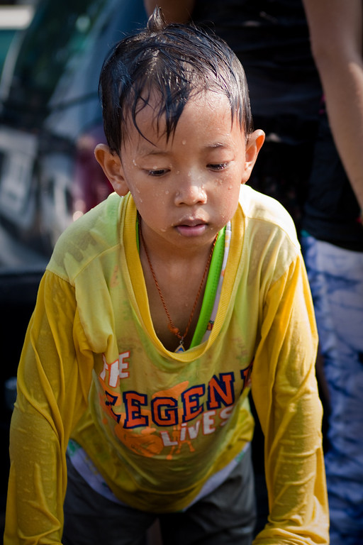 A kid feeling sick behind a truck during Songkran in Chiang Mai, Thailand