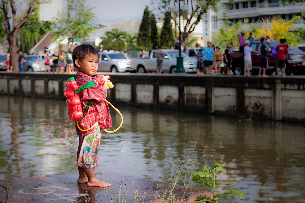 A child holding a water gun while people are partying during Songkran in Chiang Mai, Thailand.