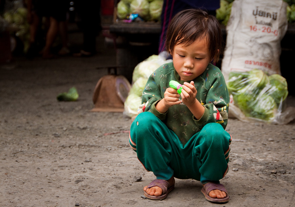 A little child playing at a local market in Chiang Mai, Thailand.