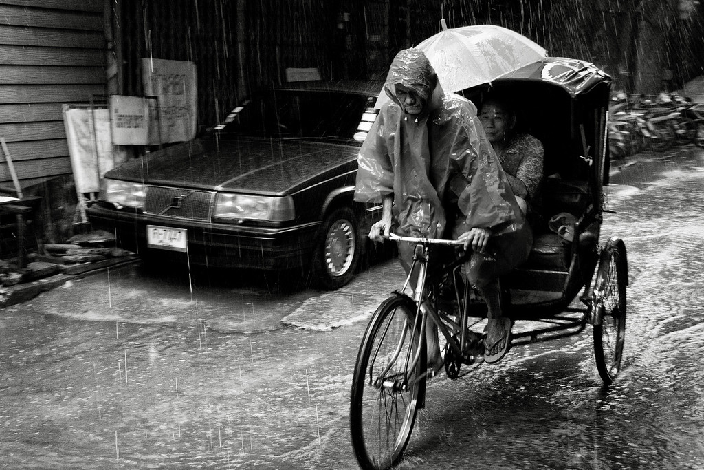 A rickshaw taxi carrying a passenger during a very rainy day in Chiang Mai, Thailand.