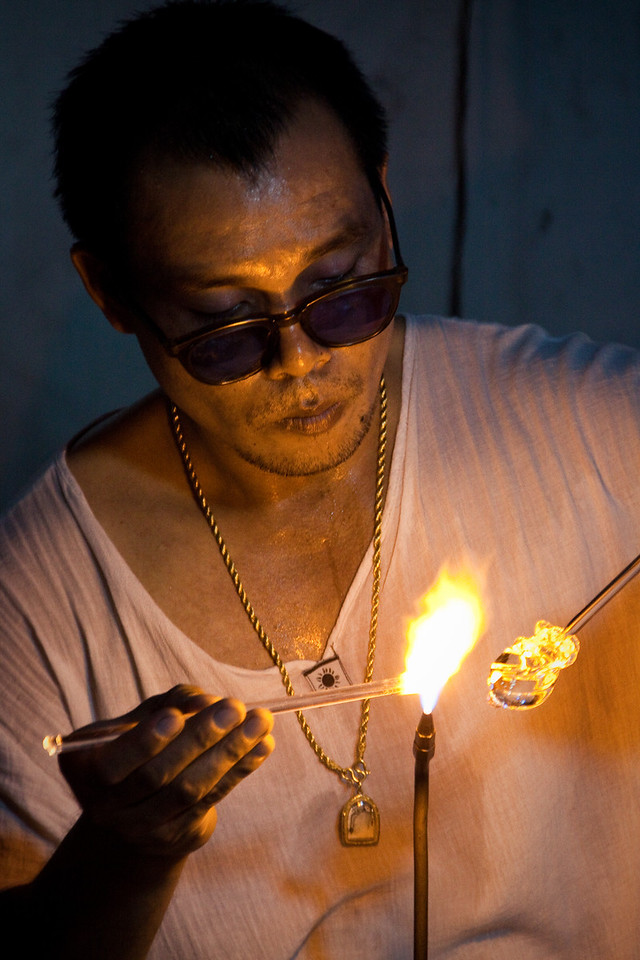 A Thai flame worker working on a glass ornament during the Sunday Walking market in Chiang Mai, Thailand.