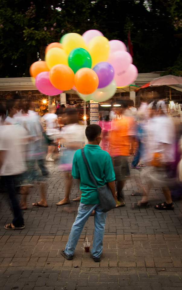 A balloon seller standing straight waiting for costumers during the busy Sunday walking Market in Chiang Mai, North of Thailand