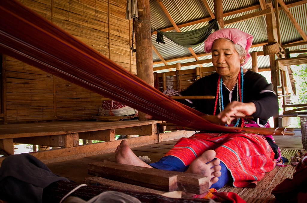 A Sgaw Hill tribe woman, also known as the White Karen, weaving a traditional piece of cloth in a village near Chiang Mai, North of Thailand