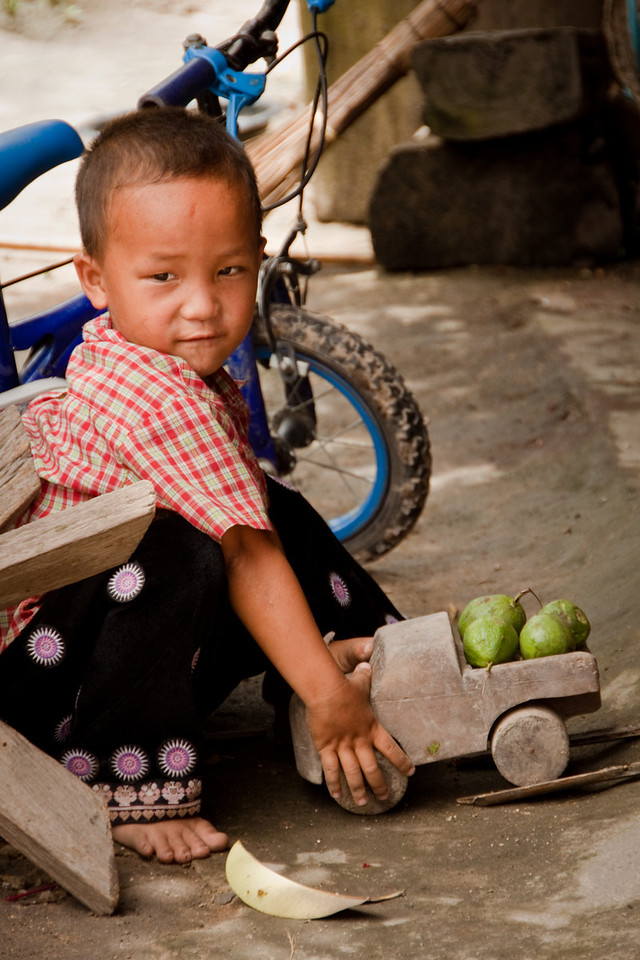 A Hmong Hill Tribe kid playing in a village with a wooden toy truck near Chiang Mai in Thailand.