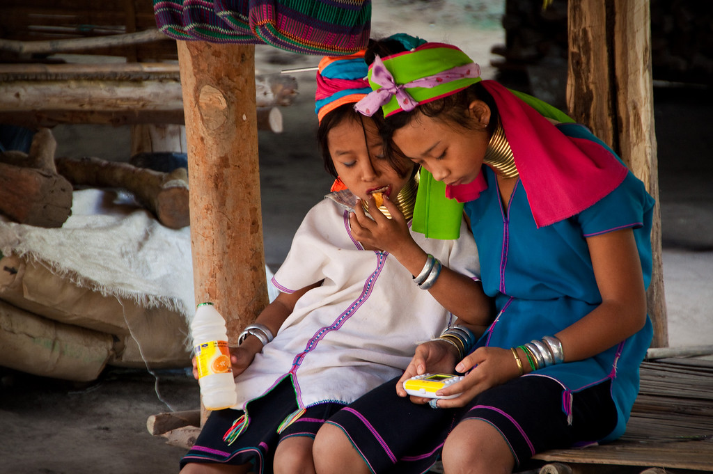 Two Kayan Tribe Long Neck gamer girls playing with an electronic game in Thailand.