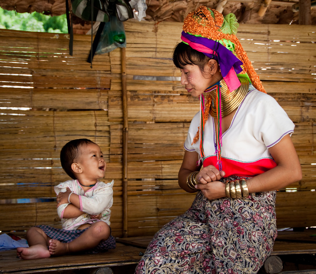A Kayan &quot;long neck&quot; hill tribe mother playing with her child near Chiang Mai, North of Thailand.