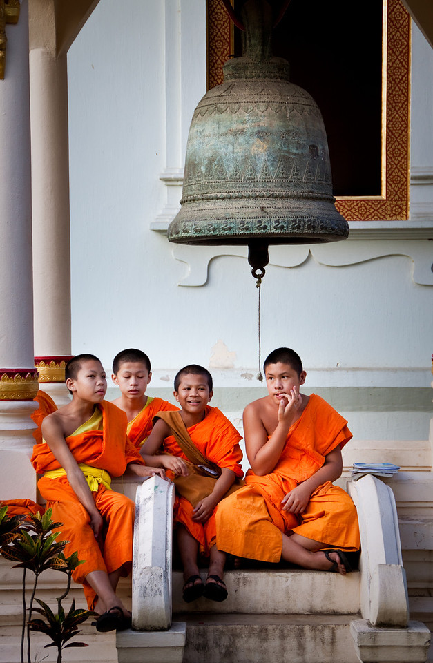 Playful young nain novice monks sitting under a bell in a Buddhist temple in Chiang Mai, Thailand