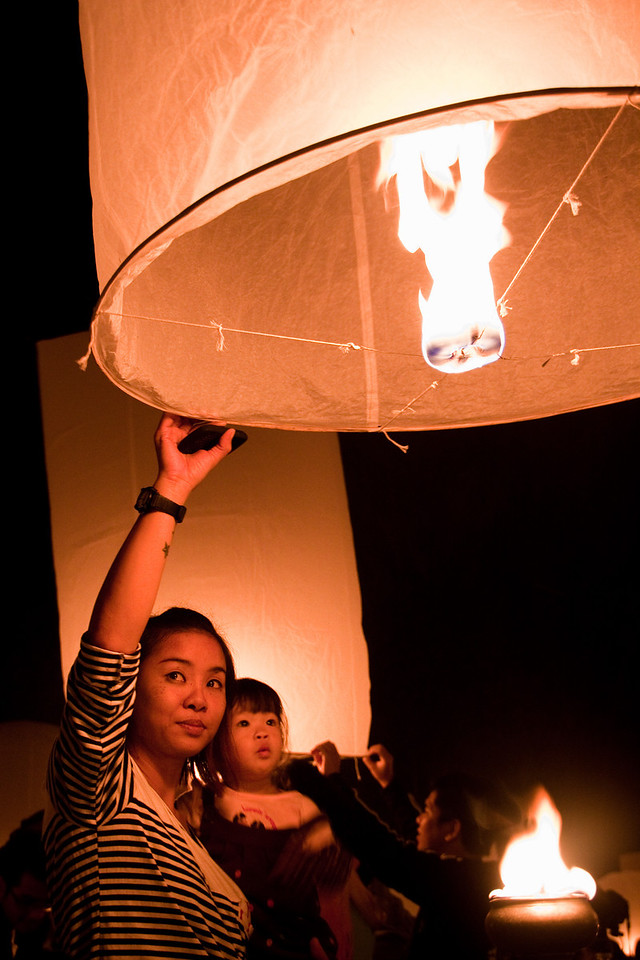 A woman holding her child and a Khom Loy lantern already lit and ready to be launched in Chiang Mai, Thailand