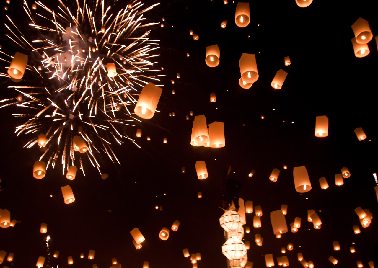 Flying lanterns in the sky with huge fireworks at the Loy Krathong festival in Mae Jo, Thailand