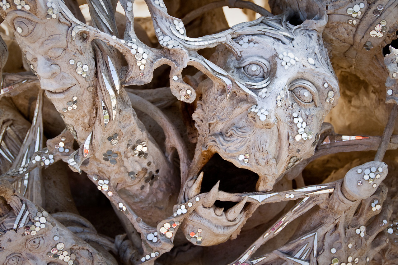 Demon faces observe and mock the visitor at the entrance of the White Temple wat rong khun in Chiang Rai, Thailand.