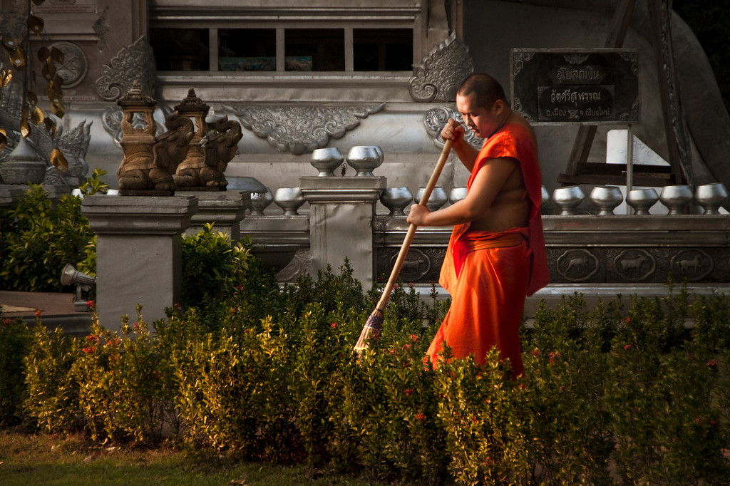 A Buddhist monk sweeping the temple grounds at sunset in Chiang Mai, Thailand.