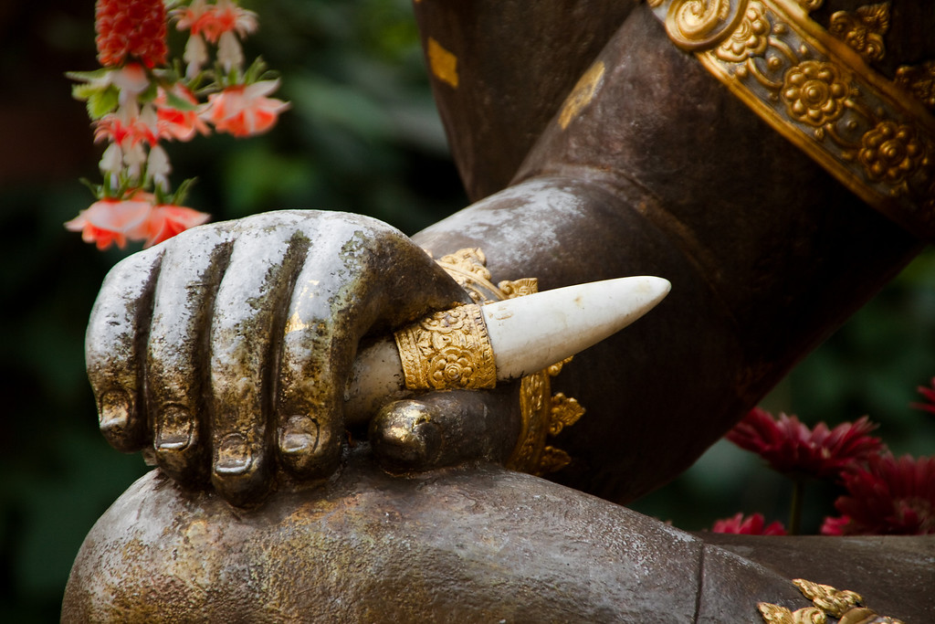 The Hindu God Ganesh's hand holding his broken right tusk in a temple in Chiang Mai, Thailand.