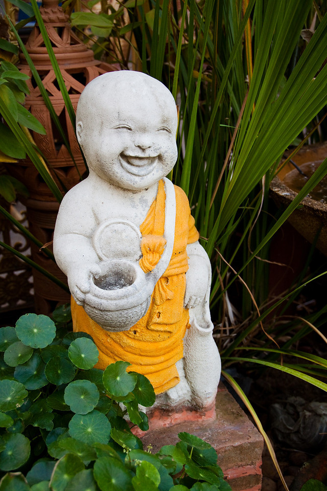 A Statuette of a happy monk asking for alms beside a temple in Chiang Mai, Thailand.