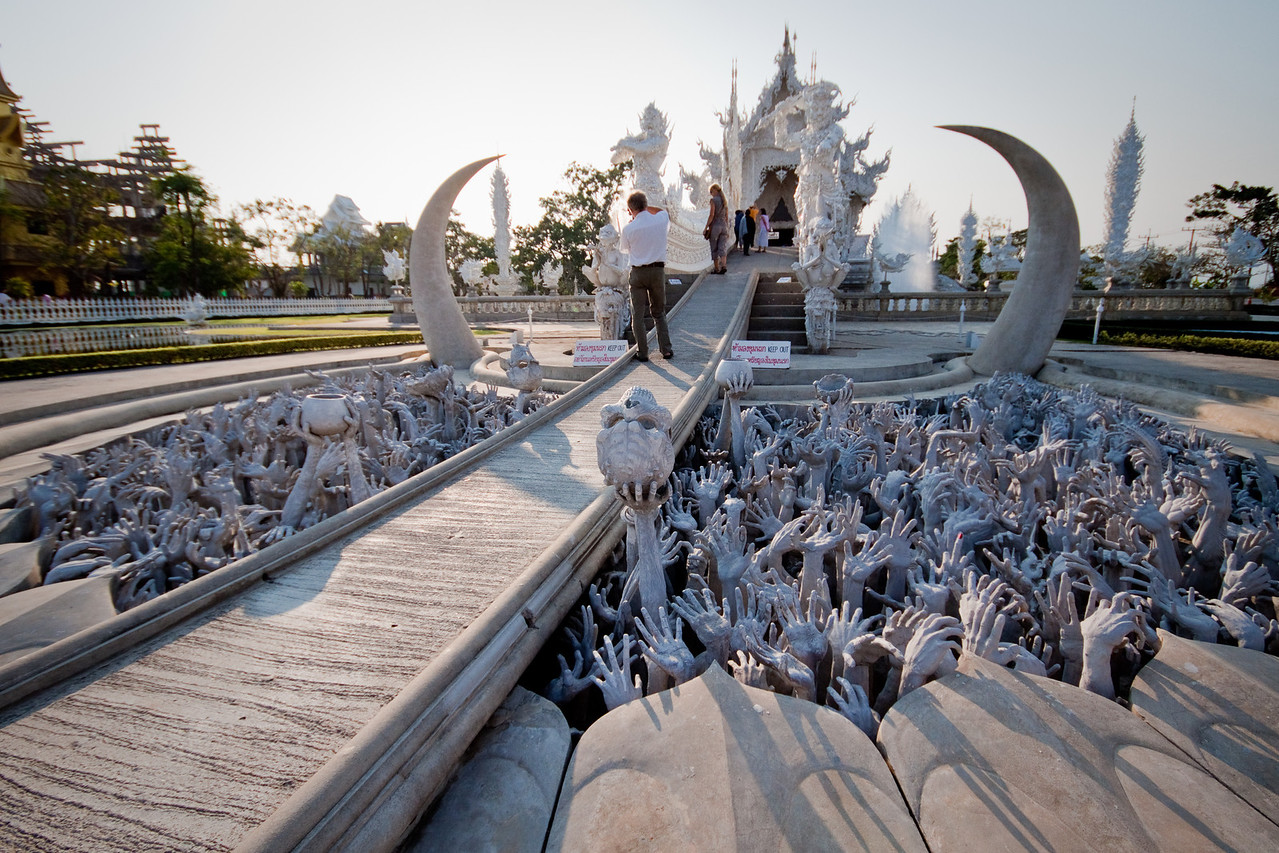 Hundreds of sculpted hands reaching up from Hell before crossing the bridge at the White Temple Wat Rong Khun in Chiang Rai, Thailand