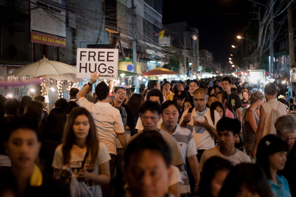 A man holding a Free Hugs sign in Chiang Mai during the Saturday Night Market in Thailand
