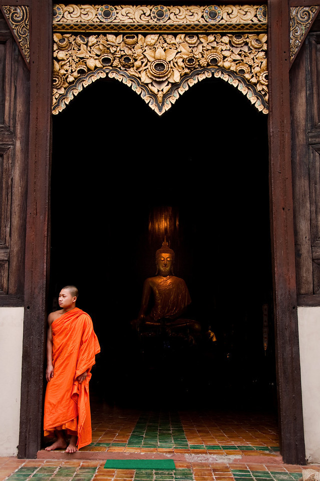 A monk standing at the entrance of a temple with the Buddha statue inside in Chiang Mai, Thailand.