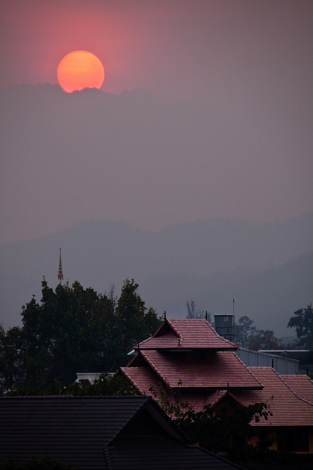 Photo of the setting sun behind the cloudy horizon over the city of Chiang Mai in Thailand