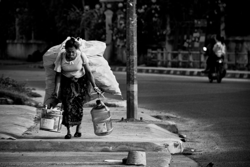 An old woman carrying a big load in Vientiane, Laos