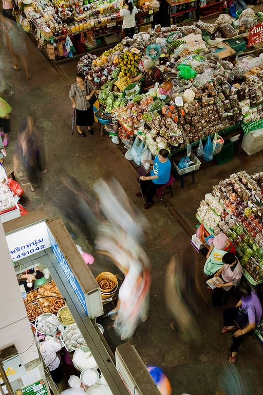 The Kad Luang Warorot Market in Chiang Mai with ghostly passers-by between the stalls.