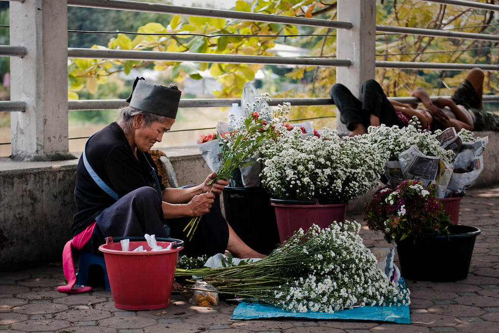 An old woman selling flowers on the street in Chiang Mai, Thailand.
