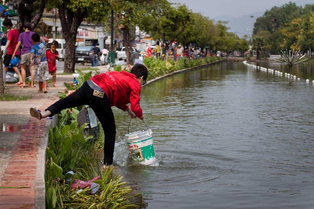 A Thai man filling his bucket to throw on passers-by during Songkran in Chiang Mai, Thailand.