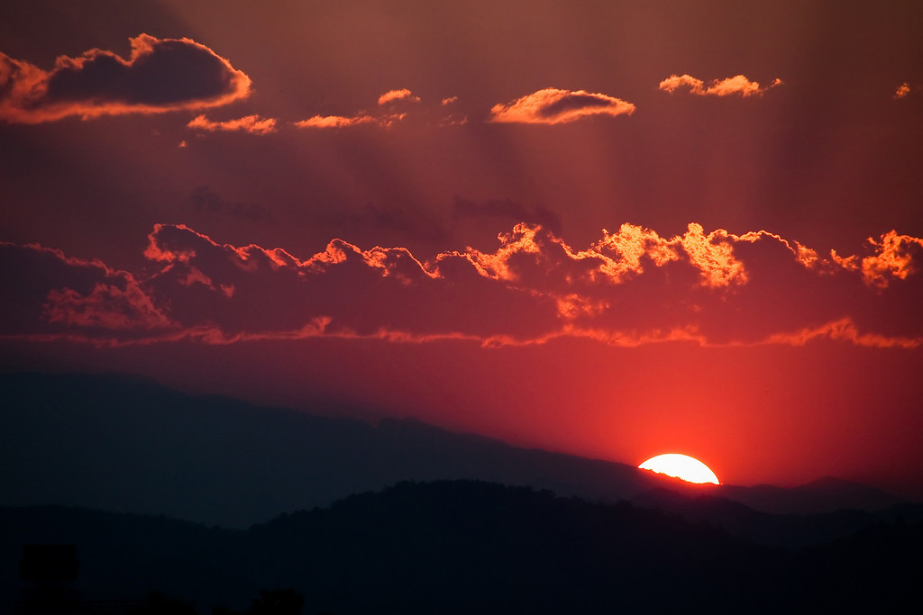 The sun setting behind the mountains in Chiang Mai, Thailand.